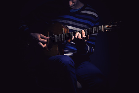 ambience: Musician and his gypsy guitar in dark blue ambience.