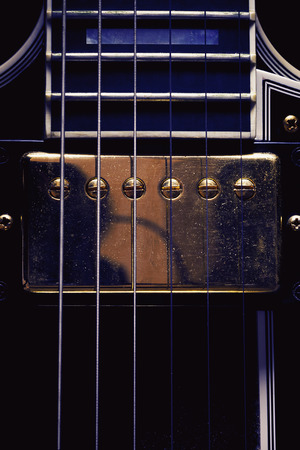double volume: Part of an electric guitar, closeup view on double pickup with dusty surface. Stock Photo