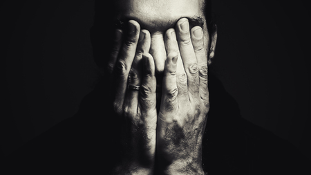 white face: Portrait of a man with hands on face, depressed expression, in black and white.