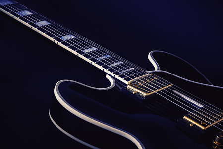 frets: Neck and body part of an electric guitar, blue background.