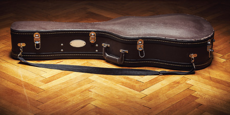 safeness: Old retro acoustic guitar suitcase on parquet. Stock Photo