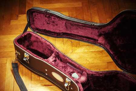 safeness: Old opened retro acoustic guitar suitcase on parquet. Details of interior.