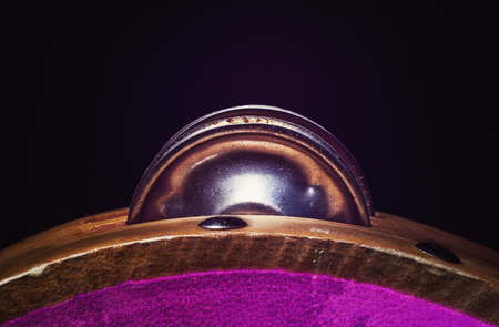 Details of a wooden tambourine, colorful illumination accentuate shapes and material.