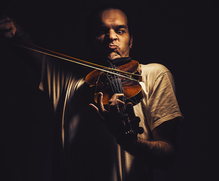 Adult man is playing a violin, in dark ambiance, showing emotions and expressions.