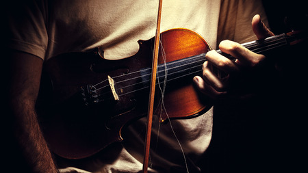 jazzy: Man is holding an old violin, closeup view on body.