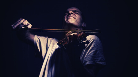 jazzy: Adult man is playing a violin, in dark ambiance, showing emotions and expressions.