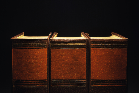 leatherette: Three old book on black background.