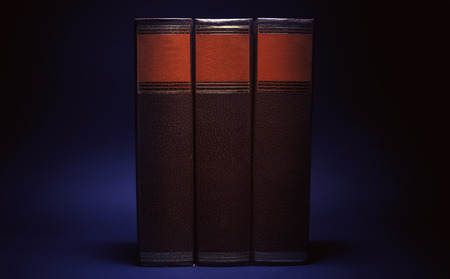 encyclopedic: Three old book on blue background.