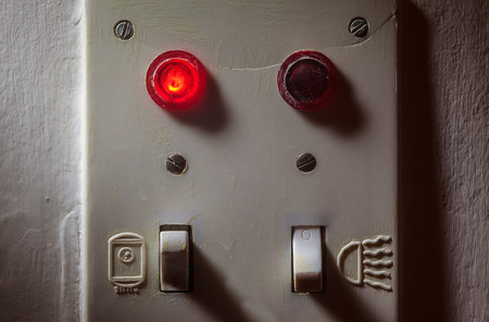 switches: Details of an old dirty plastic switches for bathroom, red light is on for boiler.