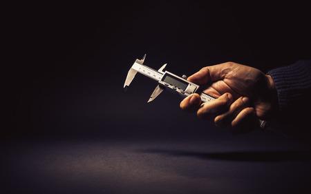 precise: Vernier caliper in male hand, conceptual composition about precise measuring.