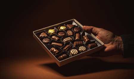 hand hold: Male hand is holding an open box of chocolates. Stock Photo