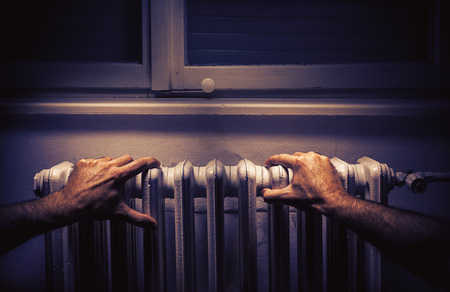 warmness: Conceptual composition about cold weather, male hands on radiator.