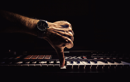 disapproval: Conceptual composition about doing something wrong, male hand symbolically in position of disapproval while hitting a key on piano.