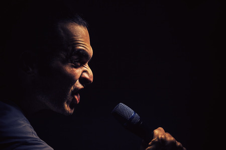 Act of a man with microphone, angry facial expression.
