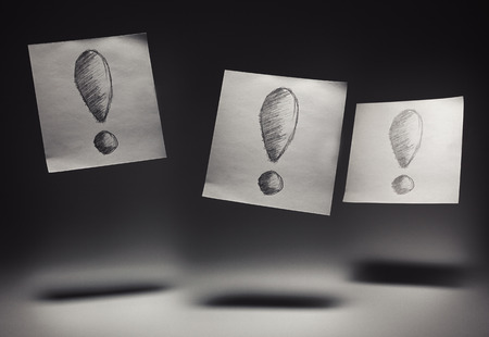 triplet: Exclamation marks drawn on paper, on gray background.