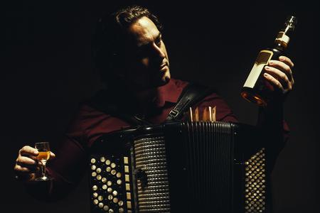 acordeon: acordeonista moderno que presenta con su armónica cromática tipo, la celebración de una botella y vaso de bebida alcohólica. Foto de archivo