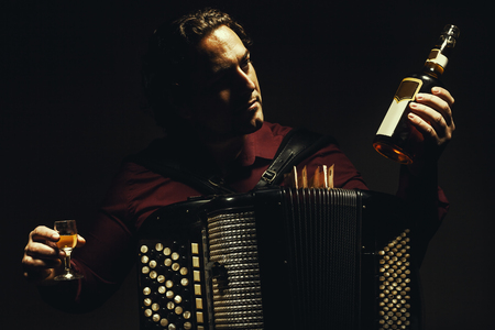 Modern accordion player posing with his chromatic harmonica type,  holding a bottle and glass of alcoholic drink.