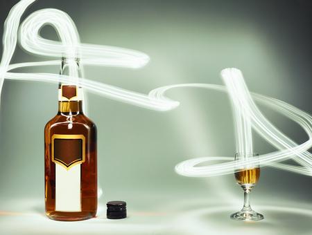 bebidas alcohÓlicas: Composición conceptual de bebidas alcohólicas, botella de coñac y una copa llena y efectos de iluminación. Foto de archivo