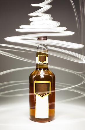 bebidas alcohÓlicas: Composición conceptual de bebidas alcohólicas, botella de coñac completa y efectos de iluminación. Foto de archivo