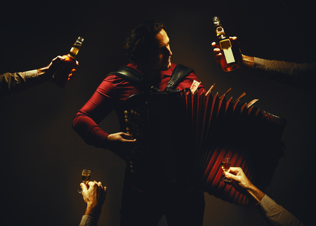 Modern accordion player posing with his chromatic harmonica type instrument, with four hands around him holding a spirit drink in bottles and glasses. Serbian money on instrument. Stock Photo