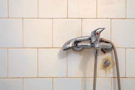 unused: Details of an old, dry and unused faucet on white bathroom tiles.