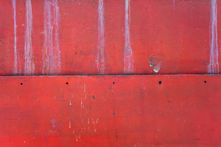 Details of red metal texture, damaged and old surface, closeup view.