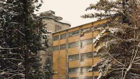 architectural exteriors: Exterior of an old factory building, winter season, view through the trees.