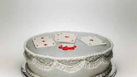 birthday decoration: Design and decoration of a 70 birthday cake, with gambling cards on top.