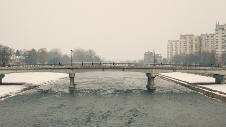 winter weather: Two bridges with lot of walkers and no cars, winter season, bad weather.