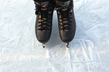 steadily: Two legs in skates on ice, winter season and sport activities.