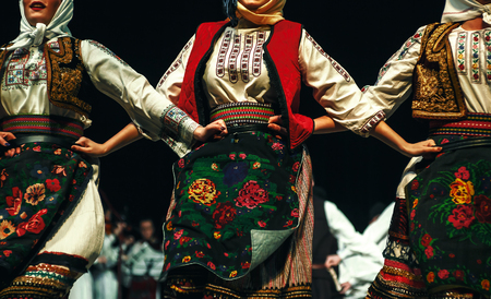 Abstract composition showing three women dressed in Serbian traditional clothe dancing in folklore.