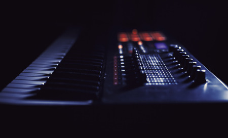 Closeup view of modern midi keyboard, dark background and strong highlights.