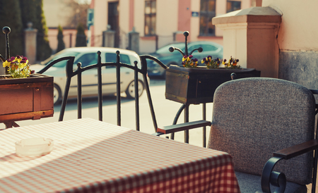 vintage objects: Sunny day while sitting in a restaurant, view on vintage furniture and street.