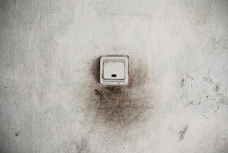 switcher: Old dirty plastic light switch and damaged wall.