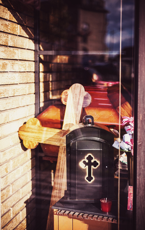 In front of shop window of funeral equipment, in style of christian tradition.