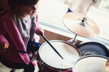 clothes interesting: Small girl is trying to play drums.