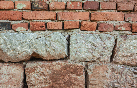 architectural exteriors: Texture details of a wall of stones and old bricks. Stock Photo