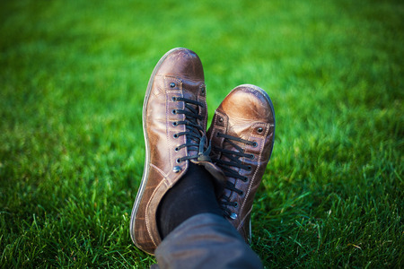 Two legs in leather shoes resting on fresh grass. Stock Photo