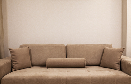 stylistic: Modern and new couch in front of wall with decorative wallpapers.