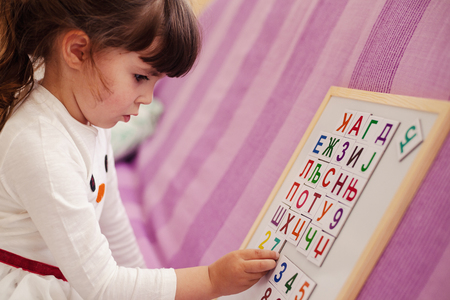 clothes interesting: Small girl is learning Cyrillic letters.