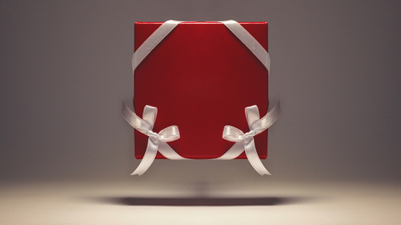 Red box ornamented with white ribbons on gray background. 스톡 콘텐츠
