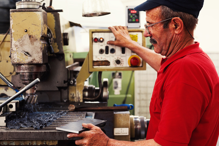 experiencing: Worker in big industrial company, producing parts on his machine.