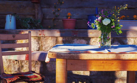 balkans: Details of village lifestyle, summer flowers in glass vase on wooden table.