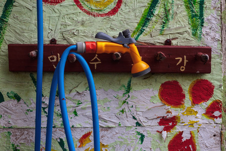 painted wood: Close-up view on colorful wall and water hose. Stock Photo