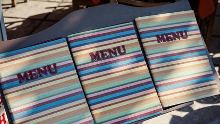 Colorful book of restaurant menu in three copies. Фото со стока