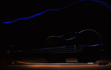 Accentuated shapes of violin with light, illuminated in dark.
