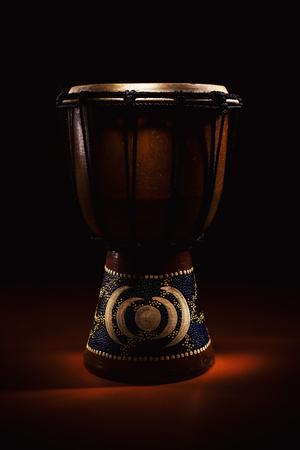 Studio shot of a small decorated djembe, illuminated in dark.
