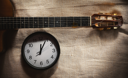 Simple composition, black wall clock on bed blanket showing twelve o'clock and part of an old retro gypsy style, acoustic guitar.