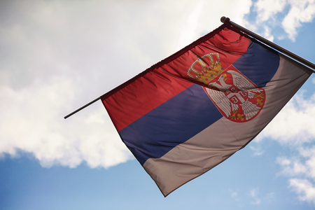 Nowadays Serbian flag, blue cloudy sky in background.