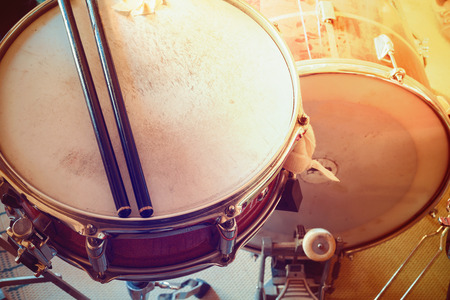 Part of an old drum kit, closeup of snare with sticks and kick drum.